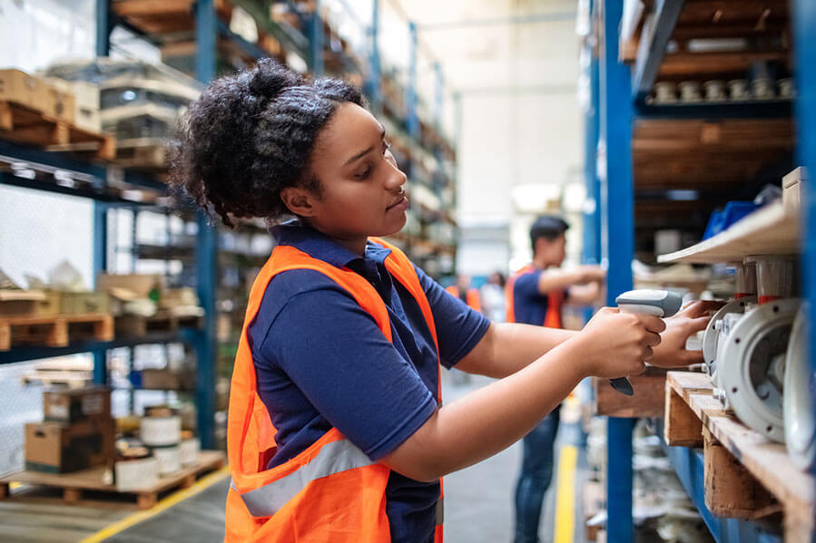 Female warehouse worker checking cargo for quality control
