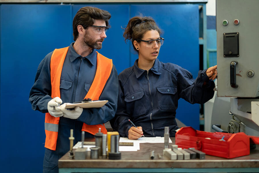 Two contract assemblers talking at a lean manufacturing plant