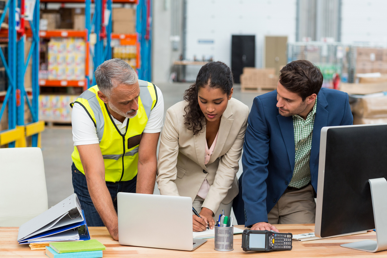 Contract manufacturers discussing lean management with laptop