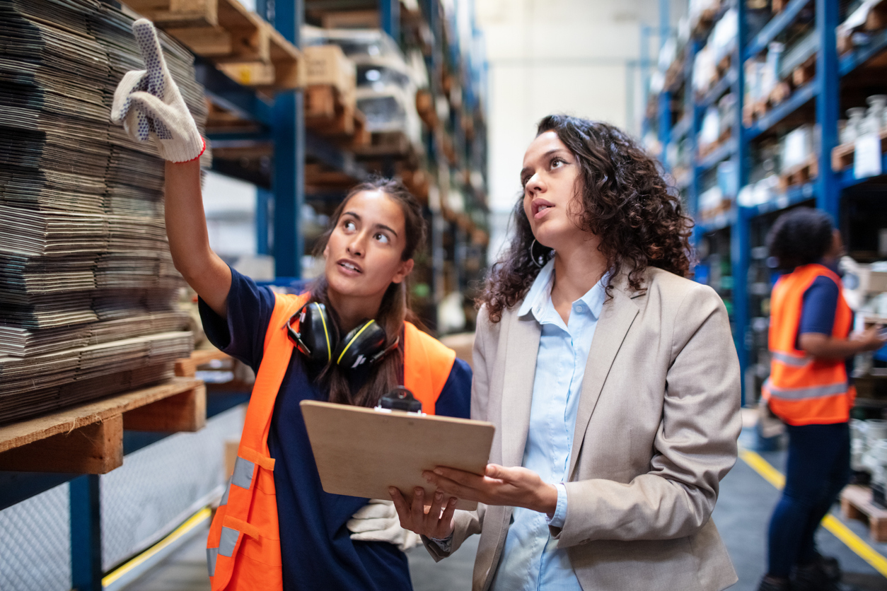 Warehouse manager with worker taking inventory for supply chain management