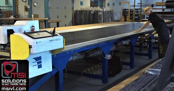 Contract manufacturer using a die cutting machine to custom cut a material